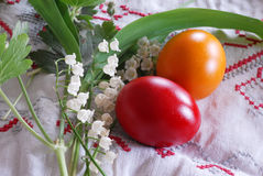 Colorful Easter eggs. Shining red and orange Easter eggs with lily of the valley plant Stock Image