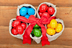 Colorful easter eggs in small burlap sacks Royalty Free Stock Images