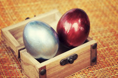 Colorful easter eggs in small coffer, vintage style image. Royalty Free Stock Photo