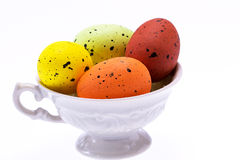 Colorful easter eggs in small cup isolated on white background Stock Photography
