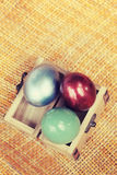 Colorful easter eggs in small wood case on bamboo weave sheet ba Royalty Free Stock Image