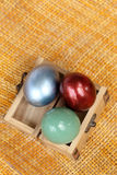 Colorful easter eggs in small wood case on bamboo weave. Stock Photos