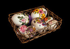 Colorful Easter eggs stacked in golden wire basket, symbol of sp Stock Photos