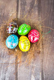 Colorful easter eggs in straw nest on a wooden table Royalty Free Stock Photography