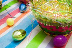 Colorful Easter Eggs on a Striped Tablecloth Near a Bright Woven Basket Stock Image