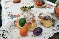 Colorful easter eggs and sweet bread. Easter traditions - colorful eggs placed in a traditional sweet bread on white linen table cloth Stock Photos