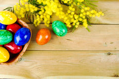 Colorful easter eggs on the table. Easter eggs and mimosa on the table Stock Photography