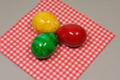Colorful easter eggs. Three colorful eggs on a red and white napkin Stock Photo
