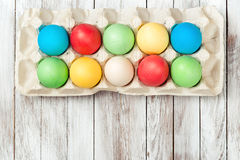 Colorful easter eggs in a tray over wooden background. Space for text. Easter card. Royalty Free Stock Images