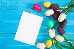 Colorful easter eggs and tulips on blue rustic wooden background. Still life. Top view. Copy space Royalty Free Stock Photos