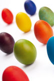 Colorful Easter eggs on white. Close up of colorful Easter eggs stood on white background, focus on green egg in center Stock Photos