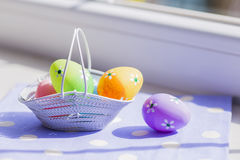 Colorful easter eggs in white basket on blue fabric near window.  Royalty Free Stock Photography