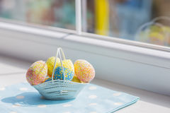 Colorful easter eggs in white basket on blue fabric near window.  Royalty Free Stock Images