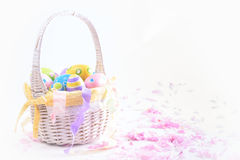 Colorful Easter eggs in white basket and pink delicate blossoms Royalty Free Stock Images