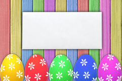Colorful Easter eggs and white envelop on painted color wooden Stock Image