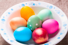 Colorful Easter eggs on white plate. On linen cloth Royalty Free Stock Images