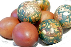 Colorful Easter eggs on white plate placed by heap Stock Image