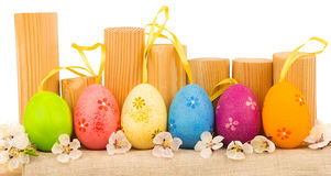 Colorful easter eggs with white spring flowers and wooden logs Stock Image