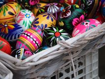Colorful easter eggs in the white Wicker basket. Colorful easter eggs. Painted eggs with flowers and various patterns. Blue, red and yellow eggs Royalty Free Stock Images