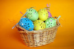 Colorful Easter Eggs in a Wicker Basket. Closeup of colorful, beautifully crafted easter eggs in a wicker basket on an orange background Stock Photo