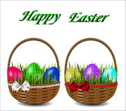 Colorful Easter eggs in a wicker basket with a bow. Stock Images