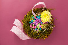 Colorful easter eggs in wicker basket with a flower Royalty Free Stock Image