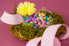 Colorful easter eggs in wicker basket with a flower Stock Photo