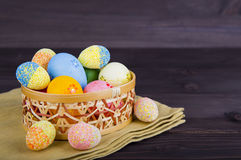 Colorful Easter eggs in wicker basket on textile on dark wooden Royalty Free Stock Photography