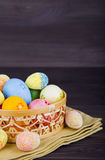 Colorful Easter eggs in wicker basket on textile on dark wooden Royalty Free Stock Images