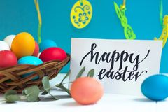 Colorful Easter eggs in a wicker basket and on a white background, text Happy Easter. Colorful Easter eggs in a wicker basket and on white background, text Happy Royalty Free Stock Image