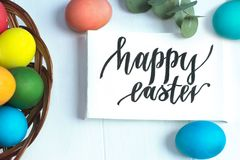 Colorful Easter eggs in a wicker basket and on a white background, text Happy Easter. Colorful Easter eggs in a wicker basket and on white background, text Happy Stock Image