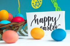 Colorful Easter eggs in a wicker basket and on a white background, text Happy Easter. Colorful Easter eggs in a wicker basket and on white background, text Happy Royalty Free Stock Photography
