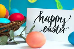 Colorful Easter eggs in a wicker basket and on a white background, text Happy Easter. Colorful Easter eggs in a wicker basket and on white background, text Happy Stock Photo