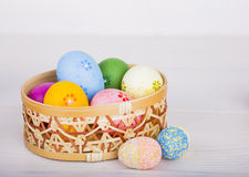Colorful Easter eggs in wicker basket on white wooden background.  Stock Images