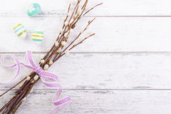Colorful Easter eggs with willow branches and lila ribbon and copy space on a wooden background Stock Photo