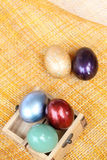 Colorful easter eggs in wood box on bamboo weave sheet Stock Photos