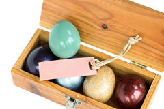 Colorful easter eggs in wood box with paper tag. Royalty Free Stock Photos
