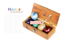 Colorful easter eggs in wood box on white background. Royalty Free Stock Images