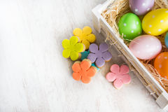 Colorful easter eggs in wooden box and homemade fondant covered flower cookies on a white wood background Royalty Free Stock Photos