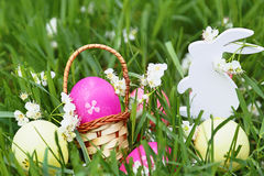 Colorful easter eggs, wooden rabbit and flowers on fresh spring grass in the garden. Royalty Free Stock Photo
