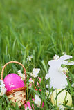 Colorful easter eggs, wooden rabbit and flowers on fresh spring grass in the garden. Stock Photography