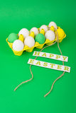 Colorful Easter eggs in yellow carton. Closeup studio shot of colorful Easter eggs in yellow carton on green background with Happy Easter text decoration Royalty Free Stock Images