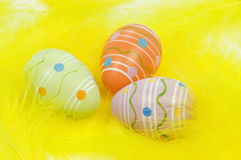 Colorful Easter eggs on yellow feathers. Painted Easter eggs on bed of yellow feathers stock images