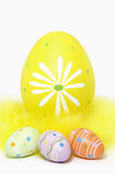 Colorful Easter Eggs and Yellow Feathers on White Background Stock Photos