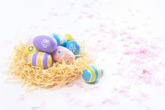 Colorful Easter eggs in yellow nest and pink blossoms Stock Image