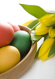 Colorful easter eggs and yellow tulips. Colorful easter eggs in wooden bowl. Some tulips in background. Space for your text stock image