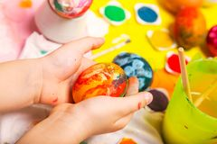 Colorful Easter painted egg in cildren hands hands. Over the work table stock image