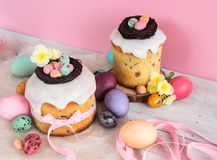 Colorful Easter spring stillife in soft light and trendy pastel colors. Traditional cake with chocolate nest, candy and qail eggs Royalty Free Stock Image