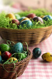 Colorful Eastern eggs in a wicker basket. Colorful chicken an quail eggs for Easter that are placed in wicker baskets with green grass on a square pattern pink Royalty Free Stock Image