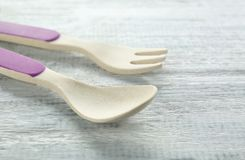 Colorful eating utensils for baby. On wooden table Stock Photo